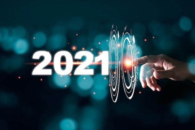 Mão tocando passar através de infográfico para 2021 ano com bokeh azul e escuro