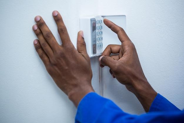 Mão tocando teclado de segurança doméstica