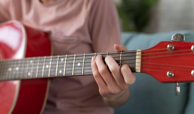 Mão tocando violão de perto