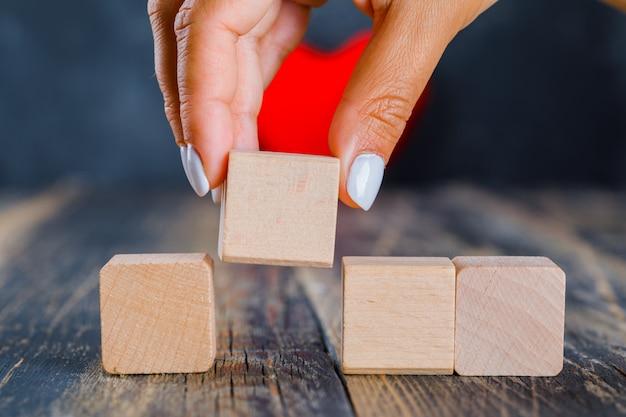 Mão tomando cubo de madeira