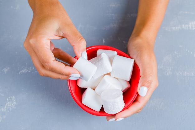 Mão tomando marshmallows doces