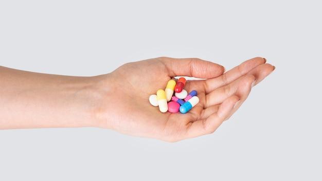 Mão tomando pílulas tratamento isolado