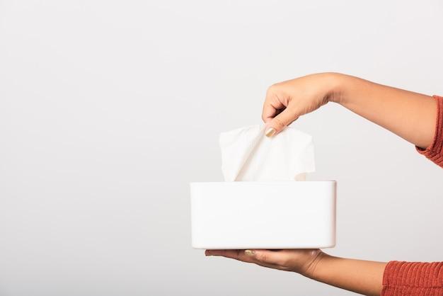 Mão tomando puxando tecido facial branco fora de uma caixa branca