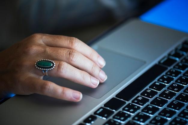 Mão trabalhando digitando no laptop