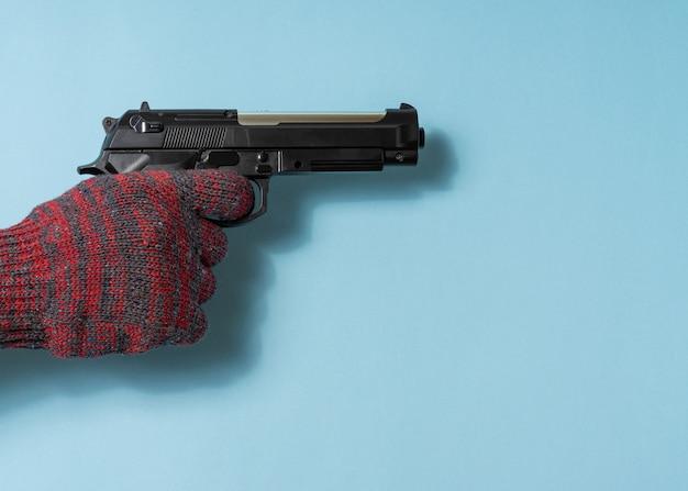 Mão um homem segura uma arma sobre fundo azul. copie o espaço.