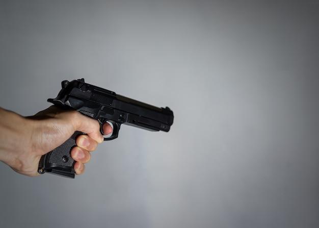 Mão um homem segurando uma pistola.