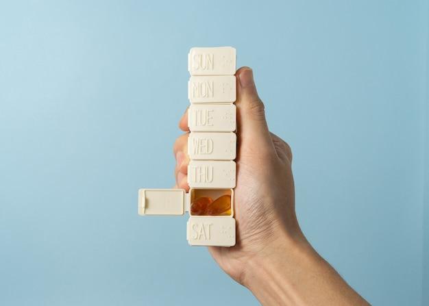Mão um homem segurar o recipiente de remédio para uma programação de dieta de uma semana.