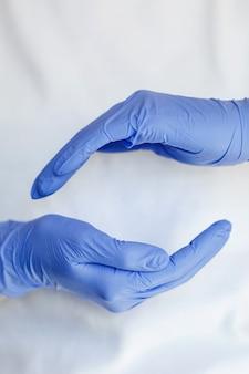Mão usa uma luva protetora para limpar ou arrumar. mão feminina calçar luva de látex isolada no fundo branco.