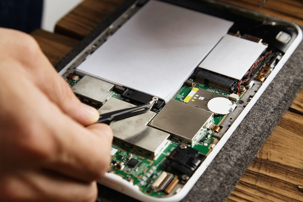 Mão usa uma pinça para pegar um pequeno grupo que segura a bateria na placa-mãe reparando serviço eletrônico quebrado