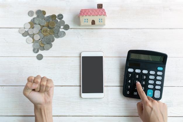 Mão usando a calculadora enquanto levantando o punho comemorando sucesso, planos de poupança para o conceito financeiro de habitação, cópia espaço, vista superior