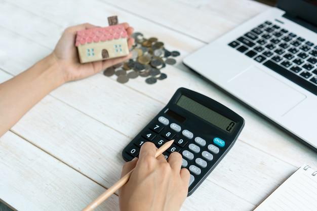 Mão usando a calculadora, mantendo o modelo da casa, notebook e computador laptop, planos de poupança para o conceito financeiro de habitação