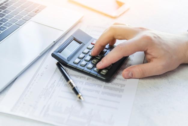 Mão, usando, calculadora, analisando, tabela, ligado, papel