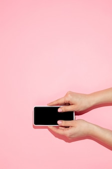 Mão usando gadget, smartphone em vista superior, tela em branco com copyspace, estilo minimalista