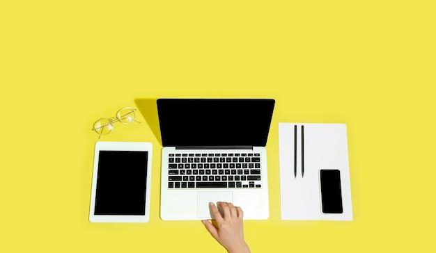 Mão usando gadgets, dispositivo em vista superior, tela em branco com copyspace, estilo minimalista, folheto