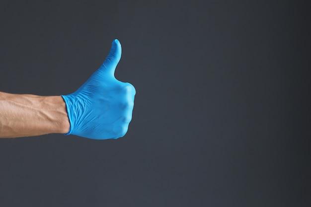 Mão usando luva de látex azul com o polegar para cima gesto em fundo escuro. copie o espaço.