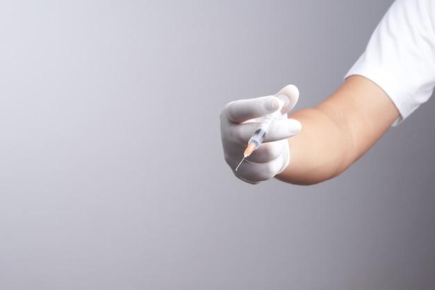 Mão usando luva de látex segurando a seringa com um medicamento