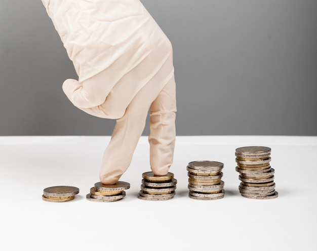Mão usando luva de proteção andando em moedas