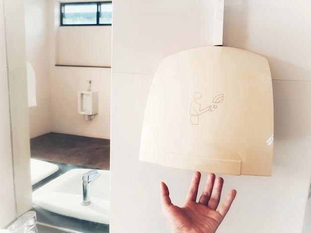 Mão usando o secador de mãos automático após o toalete para a higiene.