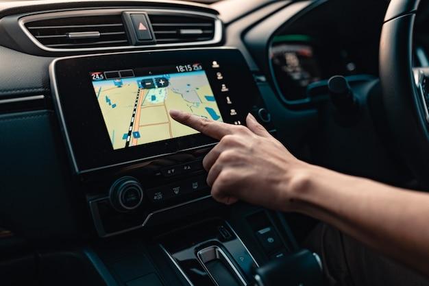Mão usando o sistema de navegação gps no carro durante a viagem