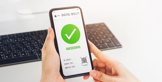 Mão usando o telefone celular para a tela de pagamento bem-sucedida