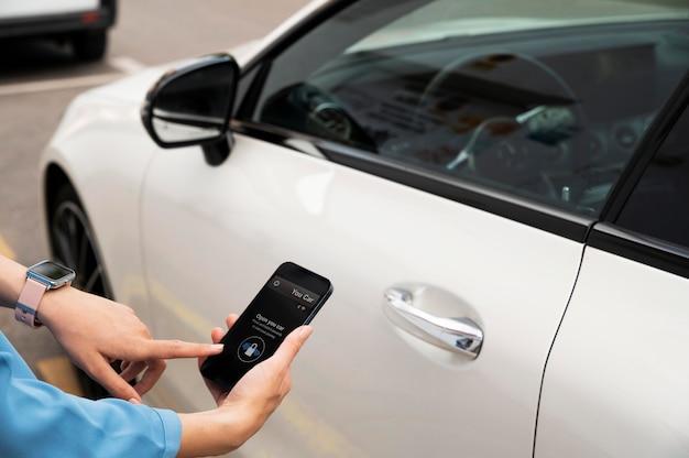 Mão usando o telefone para desbloquear o carro