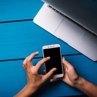 Mão, usando, smartphone, acima, azul, escrivaninha