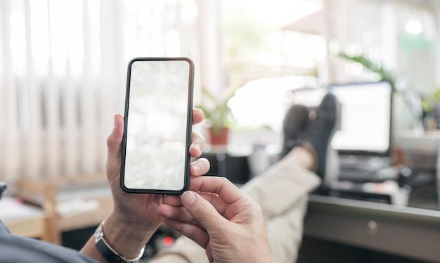 Mão usando smartphone com tela em branco
