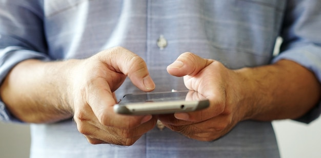 Mão usando smartphone conectando-se à internet.