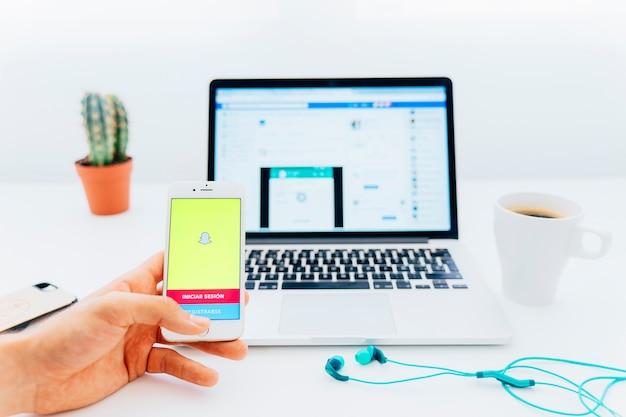 Mão usando snapchat no telefone e laptop com facebook