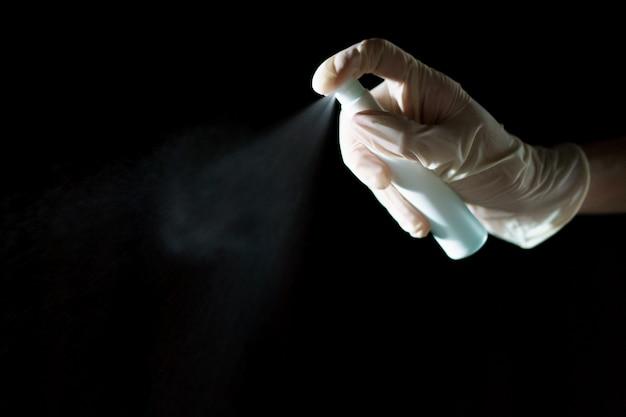 Mão usando spray desinfetante, desinfetante com álcool para parar de espalhar o coronavírus ou covid-19.