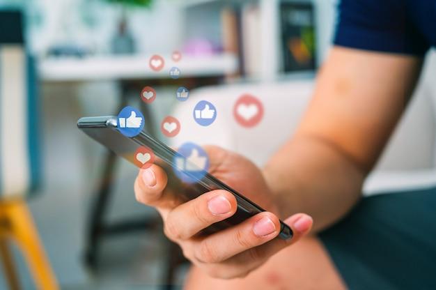 Mão usando telefone inteligente com o conceito de mídias sociais