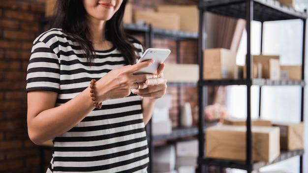 Mão usando telefone inteligente e prateleira de pacotes em segundo plano
