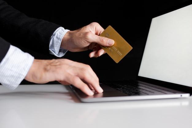 Mão usando um cartão para comprar online com laptop