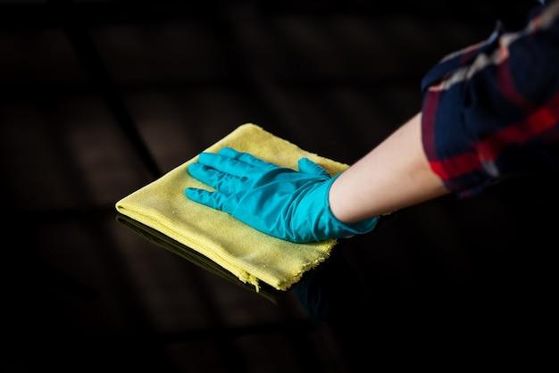 Mão usando uma luva e limpando um carro preto com um pano de microfibra amarelo