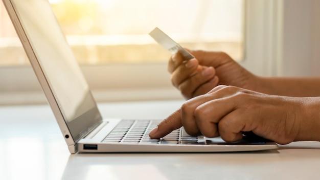 Mão usar laptop para fazer compras online e transferir o conceito de banco on-line de dinheiro de cartão de crédito.