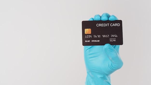 Mão usar luva médica azul segurando cartão de crédito preto sobre fundo branco.