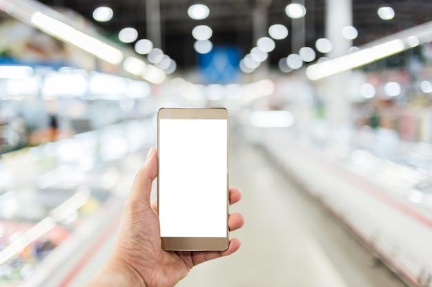 Mão usar smartphone com fundo desfocado de supermercado