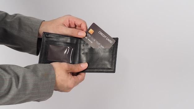 Mão usar terno cinza está segurando o cartão de crédito preto e a cor preta na carteira sobre fundo branco.