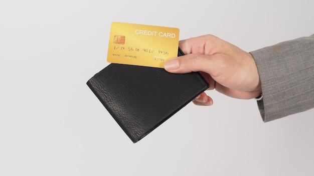 Mão usar terno cinza está segurando um cartão de crédito ouro e carteira de cor preta sobre fundo branco.