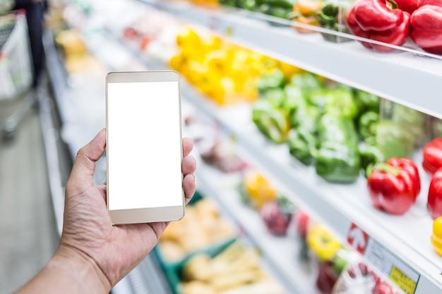 Mão, uso, smartphone, com, borrão, fundo, de, supermercado