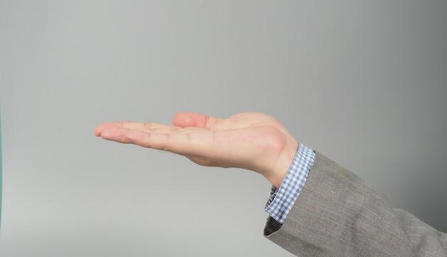 Mão vazia para segurar algo reto em um terno cinza sobre fundo cinza. tiro do empresário topic.studio.