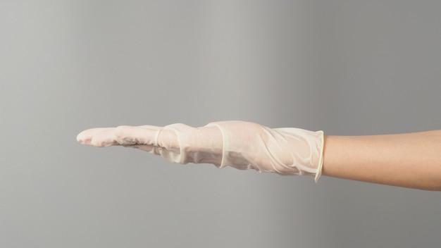 Mão vazia usando luva de látex branca ou luva médica em fundo cinza.
