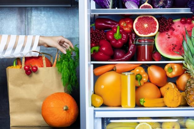 Mão vegetariana de mulher vegetariana vegetariana, colocando o pacote de papel de legumes verdes após o mercado perto da geladeira com legumes coloridos, suco cru e frutas: pimenta vermelha, laranjas, cenouras, melancia, abacaxi
