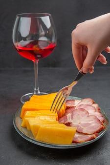 Mão vertical segurando o garfo em um prato azul com deliciosos petiscos e vinho tinto em um copo