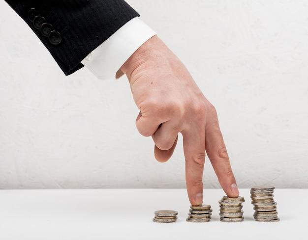 Mão vestindo uma fantasia adequada andando no conceito de moedas