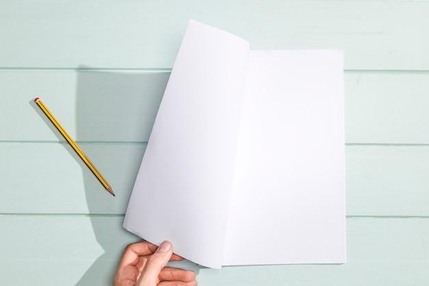 Mão virando uma página em branco plana leigos