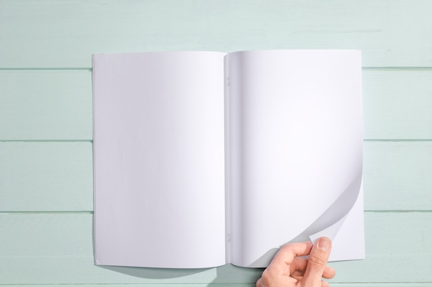 Mão virando uma vista superior da página em branco