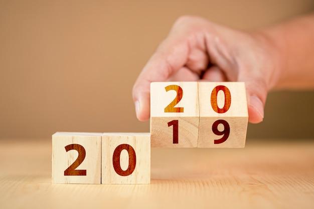 Mão virar cubo de madeira para mudança de ano novo