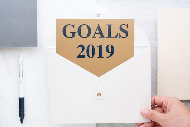 Mão vista superior, segurando, envelop, com, objetivos, 2019, ano novo, resoluções, ligado, cartão ouro