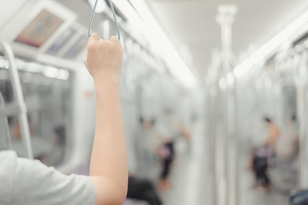 Mão viva do conceito da cidade que prende um punho dado laços no transporte público urbano